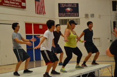 "Half-way through Zumba Night on November 8, 2013, students join one of the dance instructors up on stage. Hai Phan (11), Albert Huang (10), Derek Tin (11), instructor Ramirez, and Daniel Lam (11) enjoyed the many dance routines during the one-and-a-half hour event. ""It was really fun,"" Huang said. ""No one cared that we went on stage to dance."""