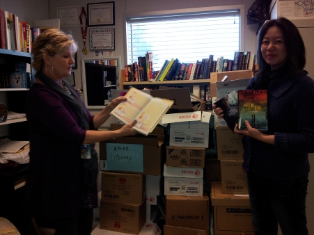 "American High's librarians, Mrs. Do and Mrs. DiFranco look through a few boxes of books sent from Scholastic. The shipments hold a large variety  to cater to all reading levels, from elementary through high school. ""It's a good thing we're the hosts, because I've already got my eye on a couple of books here, and I don't plan on letting them go!"" Mrs. DiFranco said."