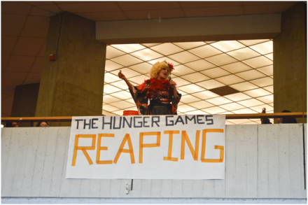 """Mrs. DiFranco, as Effie Trinket, announces the first tribute name for District 9 on Friday, November 15. Throughout the week, Mrs. DiFranco appeared at several of the lunchtime events, including the bow and arrow contest and the final obstacle course race. """"We cannot thank Mrs. DiFranco enough for dressing up as Effie Trinket and her enthusiasm for this event was truly infectious and inspiring,"""" Ma said. PC: Priscilla Ng"""