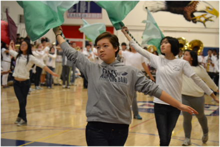 "Tanya Komrosky (12) performs with the Color Guard to the marching band's rendition of ""Christmas Carols on Parade."" ASB included many groups and clubs into the winter rally, which helped to increase the crowd's interest. ""The band was really good,"" Shing said. ""I hope that ASB includes them in more activities in the future."" PC: Priscilla Ng"