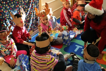 """At last year's event, senior Haarika Srinath talks with the the children of Hyman State Preschool as they open their gifts from Santa.  All of the presents were hand-packaged after school voluntarily by AHS students and included items such as coloring books, pencils, and teddy bears.  """"It's really rewarding getting to see the kids,"""" Srinath said.  'We stay there for ten to twenty minutes and read and talk with them.  They can talk about anything--like their dog or their favorite color.""""  PC: Diane Zhou"""