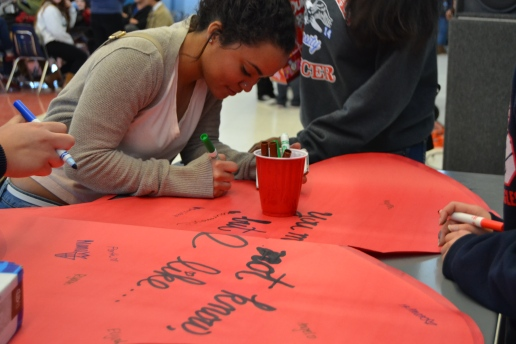 "Senior Tallulah Johnson writes down the name of her crush during lunch on Tuesday, February 11, 2014.  The ""Free Kisses"" booth was there all week and attracted a lot of curious students.  ""We were going to post [the names] but since it's after Valentine's Day, I don't think we'll be doing that,"" senior Maggie Chan said. PC: Caroline Lee"