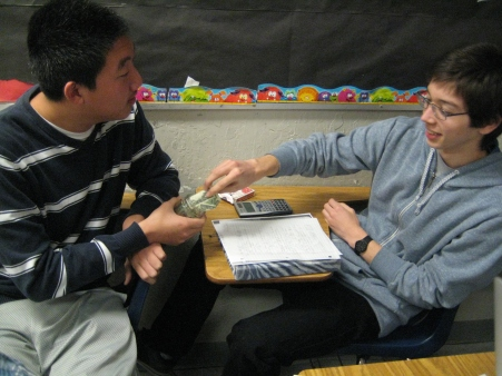 """Roger Lee hands around a small donation jar while senior Matthew Downing donates $1. The UNICEF officers collected donations in front of SAC and passed around donation jars during class. """"We'd like to thank everyone who came to donate for the cause,"""" Lee said. """"Hopefully, we can continue to be successful in future projects."""" PC: Priscilla Ng"""