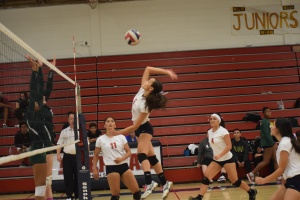 """On October 21, 2014 in the home game against Moreau, center player, junior Devon Pierre (5) spikes the ball across the net. """"I don't think of anything on the court, all my stress goes away and all I think about is volleyball,"""" Pierre said."""