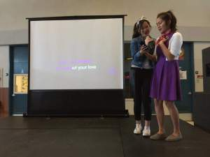 "Courtney Cheung (11) and Francesca De Las Alas (12) volunteer to sing in the ""Throwback Thursday Karaoke"" during lunch. The karaoke event was contingent to the dress up day, called Decades, in which students dressed in outfits from their favorite era."
