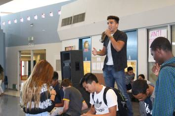 Emcee Anthony Lopez (12) explains the significance of the lunchtime activity in the rotunda while David Lee (11), Austin Beard (12), and two other students squeeze toothpaste onto plates to model the permanence of hurtful words and actions on Friday, October 9, 2015.